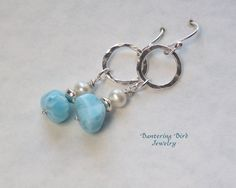 Nuggets of Caribbean blue larimar dangle with white freshwater pearls beneath hammered fine silver (.999) rings in these 2 long earrings.  Silky, sky blue larimar is found only in the Dominican Republic, and these sizeable nuggets (10-12 mm) exhibit the stones characteristic marbling-- just lovely paired with high quality (AAA) white freshwater pearls (4 x 5 mm) and sterling silver beads! A beautiful gift to yourself or a special woman in your life.  The fine silver rings are 13 mm and…