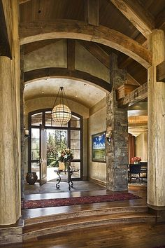 Hand-hewn beams curve above this rustic entryway for an impression that lasts.
