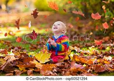 Kids play in autumn park. children throwing yellow and red leaves.baby with oak