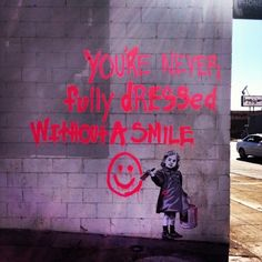 """LA Street Art. Little girl """"paints"""" a quote from the musical Annie -- """"You're never fully dressed without a smile."""""""