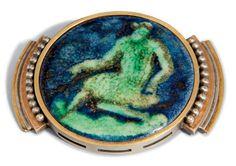 JEAN DESPRES (1889-1980) ET JEAN MAYODON (1893-1967) BROCHE, 1937 Le médaillon en céramique émaillée, à décor d'un nu masculin vert sur fond bleu, serti dans une monture en argent plaquée d'or jaune au pourtour ajouré de rectangles, flanquée de deux éléments rayonnants à gradins plaqués d'or jaune et d'or rose et soulignés d'un rang de perles 5,5 x 7,3 cm. (2 1/8 x 2 7/8 in.) Le médaillon monogrammé MJ et daté 1937 au revers, la monture signée J. Desprès avec le poinçon français d'or et…