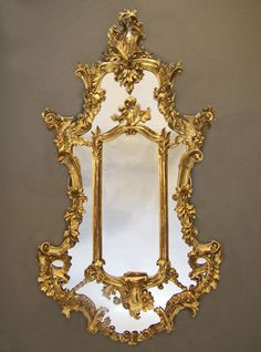 This mirror, like the walls of Rococo style interiors, is adorned with intricate gold shapes that convey sophistication.