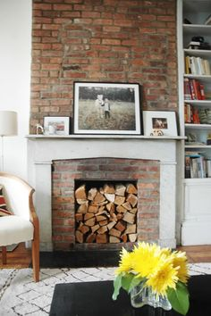 Stacked wood in nonworking fireplace. Also Union Jack pillow!