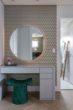 Decoração de apartamento moderno e cinza. No banheiro, lavabo, com revestimento, papel de parede, espelho redondo com iluminação indireta e flores para decorar.