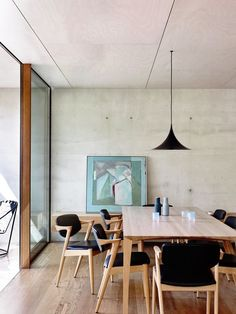 Concrete walls in dining room with modern light fixture, midcentury chairs, and abstract art
