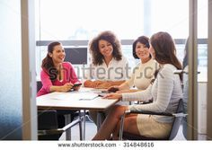 Casually dressed female colleagues talking in a meeting room - stock photo