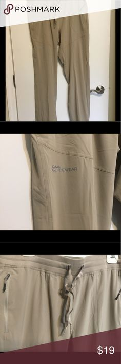CABELAS GUIDEWEAR WOMENS KHAKI STRETCH SZ L LIKE NEW CABELA'S GUIDWEAR THIN KHAKI PANTS. WOMENS SIZE LARGE. BUILT IN TIE ON WAIST. 2 ZIP SIDE POCKETS. REALY GREAT PAIR OF PANTS. MATERIAL IS LIKE A STRETCH PARACHUTE MATERIAL... SUPER COMFY! Cabela's Pants
