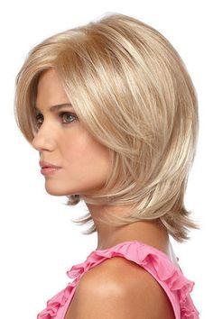 La coiffure portée par cette jeune femme est assez simple, ce qui ne l'empêche pas d'être jolie. À l'arrière, ses cheveux mi-longs descendent dans le cou et le coiffeur a ramené quelques mèches vers l'avant. Une longue frange traverse le front et en dégage une partie. La coloration blonde est très réussie.