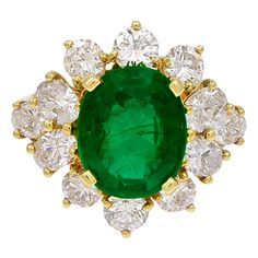 Kurt Wayne Oval Emerald Diamond Ring  A stunning ring designed by Kurt Wayne. The beautiful green oval emerald is 3.90cts, surrounded by 12 oval and round brilliant diamonds of E-F color, VS clarity, weighing 2.34cts total, in 18k yellow gold.