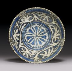 A TIMURID POTTERY BOWL NORTH IRAN OR CENTRAL ASIA, 15TH CENTURY On short foot with curved sides and slightly flaring rim, the white ground painted in cobalt-blue and black, with a central stellar motif, the cavetto with scrolling vine set on a blue and black dotted background, the rim with a band of hatching interspersed with geometric cartouches