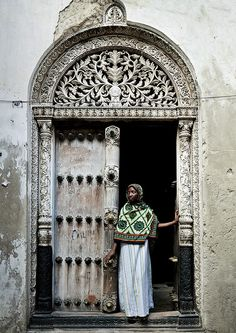 Veiled woman in front of a door in Stone Town, Zanzibar, Tanzania