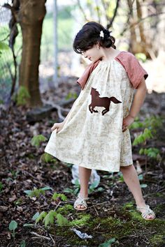 A pillowcase dress with buttoned on capelet sleeves. Imagine it in a little heavier fabric for fall/winter? sooo cute