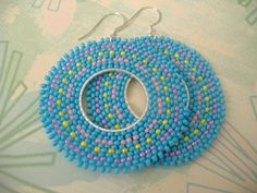 Beadwork hoop earrings. Large seed bead earrings with lots of pastel bling made with light blue, yellow, pink and lavender 11.0 seed beads. Over 600 individually hand sewn beads expertly woven to make thsee beautiful earrings. The french hook earwires and findings are sterling silver.  These very lightweight earrings measure 2.5 inches total. The hoops are 2 inches.  Great for daywear and perfect for any occasion. Shipped in a cotton filled gift box for your convenience.  Please see below…