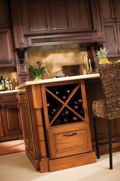 """An """"X"""" wine rack in the island offers convenient wine storage and added detail for your kitchen design. Cabinetry Shown with the Montego styled doors, in Lyptus with Heavy Heirloom """"C"""" finish. (Dura Supreme XBD)"""