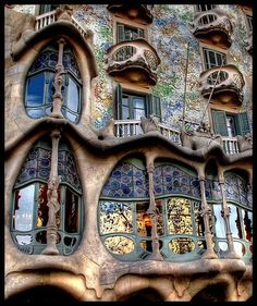 Casa Battló  The ground floor is  astonishing with tracery, irregular oval windows and flowing sculpted stone work.  It seems that the goal of the designer was to avoid straight lines completely. Much of the façade is decorated with a mosaic made of broken ceramic tiles (trencadís) that starts in shades of golden orange moving into greenish blues (Antoni Gaudi, Barcelona, Spain)