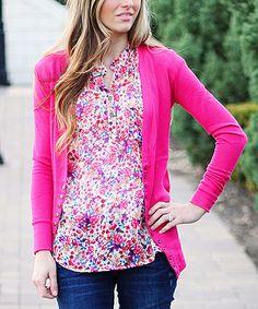 Bright pink cardigan, floral top, and dark denim