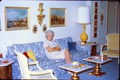 Not sure if it's 1970s, but I love it all: the chinoiserie couch, the old oil paintings next to the modern vase lamp, the woman's blue hair to match to room.