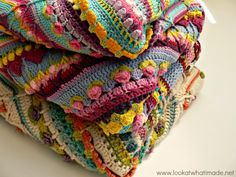 a vibrant stack of folded crochet blankets showing intricate stitches