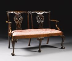 A George II mahogany double back chair settee circa 1750 with foliate scrolled crest rail and pierced foliate carved interlaced vase shaped splat, with acanthus carved arms and drop in seat, on cabriole legs with claw and ball feet