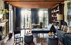 In the living room at the Mexico retreat of Andrew Fisher and Jeffry Weisman, pine beams highlight the ceiling, and the French doors feature curtains of a Duralee velvet trimmed with an ikat by Kravet.
