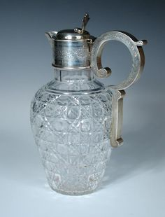 A late Victorian silver mounted glass claret jug. by William Devenport, Birmingham 1900, the baluster shaped clear cut glass body with silver mount engraved with arabesques, stylised scroll handle and hinged cover with trefoil handle, 24cm  - Cheffins