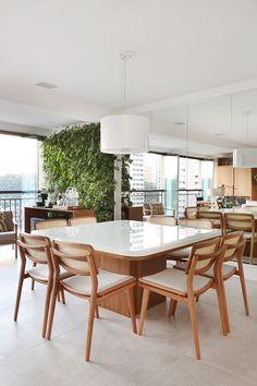 Decoração de apartamento integrado e com crianças. Mesa de jantar de madeira, parede espelhada e luz natural.
