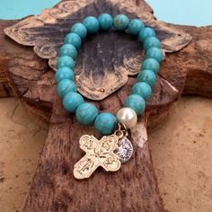 Turquoise stretch Bracelet with Cross Stretch bracelet with turquoise colored beads. Has a cross dangle and extra charm. All sales final Jewelry Bracelets