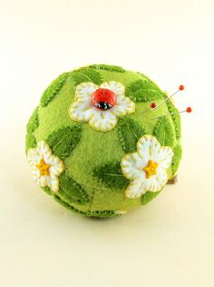"""❤ 2013 OOAK Janie Comito~ Ladybug & White Flowers~ Pin Cushion- The gusseted wool felt pin cushion, measuring 3"""" wide by 2"""" tall, is firmly filled with chopped wool felt & wool fiber & with appliqued stylized wool felt flowers, leaves & buds.  The flower centers are yellow plastic star buttons. The red glass ladybug button looks to be hand detailed, then fired; it measures 1/2"""" across. ~By jraggedybear"""