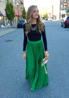 Shop this look on Lookastic:  https://lookastic.com/women/looks/long-sleeve-t-shirt-maxi-skirt-clutch-necklace-bracelet/13223  — Multi colored Necklace  — Black Long Sleeve T-shirt  — Gold Bracelet  — Gold Leather Clutch  — Green Pleated Maxi Skirt