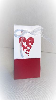 """A gift box/bag made from quality card stock. Falling heartdesign.It measures 5"""" tall 2.25"""" wide and 1.5"""" depth    There are wedding cards/Invitationsto match shown in pictures (DISCOUNT if you buy together with box) use the code (Wedding)    There are other colours available so please get in touch if you have a particular colour you want and we will make to order.    Colours shown are Red and Cookie 