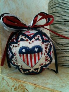 Folded fabric Americana Ornament in Red, blue and cream colors Ribbons compliment and really make the ornament ! Measures 3 around, light weight.
