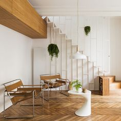 A white metal-framed staircase connects the two floors of this Parisian apartment, which local studio Les Ateliers Tristan & Sagitta has overhauled