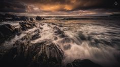 Breaking Sunset - A long exposure, landscape image of waves crashing against the rocks at Sandend in Aberdeenshire, Scotland, at sunset.