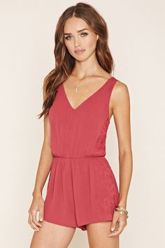 A sleeveless woven crepe romper with a V-neckline, an elasticized waist, tonal floral-embroidered sides, and a V-cutout back.