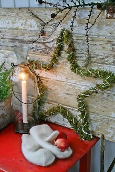 Nice star wreath with moss on a star form and fastened by wrapping string. Red or jute cord would look nice too. I like the way the old board with peeling paint is used as a backdrop and the vignette is placed on a red table.