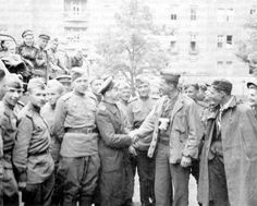"""July 4, 1945: US Forces enter the city of BERLIN, Germany and prepare to occupy the city (until 1991) as part of Post World War II agreements on the governing of Germany and its capital, Berlin. In this photo """"Soviet troops greet Signal Corps photographer who was one o f the first Americans into the city..."""""""