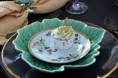 mesa posta com sousplat transparente com borda dourada. prato raso verde em forma de folha e prato de sobremesa branco com estampa floral. Para decorar um cupcake ao centro.