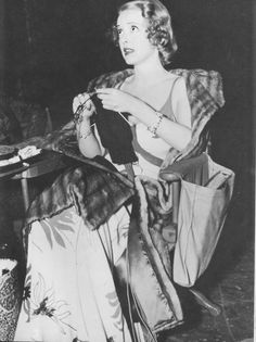 Bette Davis, gowned for her role in Kid Galahad (1937), takes advantage of a break in filming with her knitting.