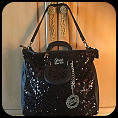 "Stunning Italian oversized black sequin bag Stunning oversized sequins bag. This luxurious bag is fully embellished with black sequins, silver hardware, double handles, removable shoulder strap and deep exterior zipper pocket with a huge pull. Silver hardware consists of Secret Pon-Pon insignia, silver 6 1/2"" chain and large charm that reads ""BELIEVE WE CAN CHANGE IT.""  Interior of bag is red velvet and has 3 pockets, including a zippered pocket and cell phone pocket. Black leather side…"