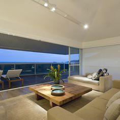 Vista da sala de estar com a paisagem litorânea ao funto. Design by Renata Basques.