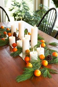 Place pillar candles, evergreen branches, pinecones and clementines on a beveled-edge mirror. More Thanksgiving centerpieces: http://www.midwestliving.com/homes/seasonal-decorating/holiday-ideas/easy-thanksgiving-centerpieces/?page=2