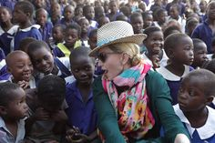 U.S singer Madonna chats with children in Kasungu, about 150 kilometers north of the capital Lilongwe, Sunday, Nov. 30, 2014. Madonna is currently visiting Malawi with her son David and daughter Mercy, where she has been working since 2006 with her non profit organization, Raising Malawi. (AP Photo/Tsvangirayi Mukwazhi)