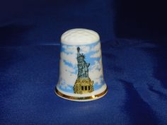 Statue of Liberty (NYC) Souvenir Thimble - Porcelain/Back:  Give me your tired,  Your Poor,  Your Huddled Masses Yearning to Breathe Free The world's most famous symbol of freedom and liberty Started 1875 Finished 1886 Height of 302ft (92m)