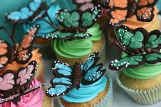 butterfly cupcakes! the butterflies are very very easy to do. you need to melt baking wafers(i got mine at hobby lobby) in a bag in the microwave, cut the corner of the baggie...draw a butterfly pattern to trace over with parchment paper...trace the butterfly with the molds, blend together with toothpicks, and apply any sprinkles you want, then put em all together.