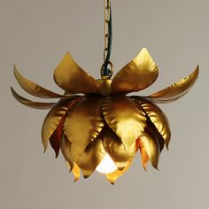 A unique artistic statement, our Gold Lotus Hanging Pendant Lamp is handcrafted in India of metal petals welded together to form a gold lotus blossom. The petals nestle around a light bulb to create a peaceful and romantic effect for the entryway or bedroom.