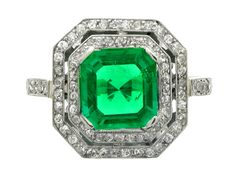 Emerald and diamond octagonal cluster ring, circa 1920. A platinum ring set with one central square emerald-cut emerald in a claw setting with an approximate weight of 1.50 carats, encircled by two concentric conforming single rows of round old cut diamonds in millegrain bead settings and with a pierced divide, above an ornate openwork double arcaded gallery, flanked by raised shoulders set with single rows of round old cut diamonds in millegrain bead settings, all seventy six diamonds with…