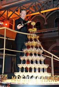 Benedict Cumberbatch with a giant champagne tower at some awards ceremony