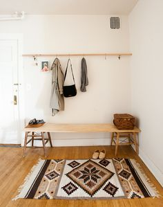 Not all homes have a transitional space. We like this solution from Ashley Helvey and Miles Pederson in Seattle spotted on Design Sponge. Two old stools are used as a base for this entry bench and a wooden pole straddling two hooks (with S hooks hanging from it) serves as a coat rack.