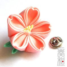 This is a kanzashi lapel pin made of folded silk. So adorable.