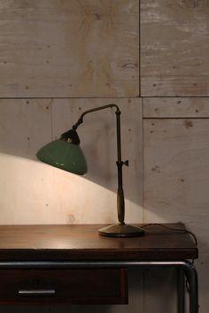 """Lampada ministeriale anni 30, in ottone con inserto di legno nel manico e cappello in lamiera colorata di verde. La lampada è regolabile per direzionare la luce tramite """"farfalline"""" in ottone lungo i braccetti. Elegante si addice a qualsiasi scrivania o tavolo da lavoro. Funzionante."""
